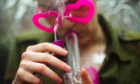 A woman smokes marijuana from a bong before The Global Marijuana March in Toronto