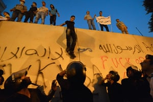 Benghazi protest: Protesters climb down from the wall of the US embassy in Cairo