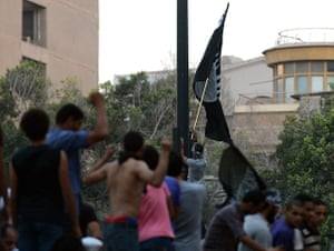 Benghazi protest: Egyptian protesters raise a black flag inside the US embassy