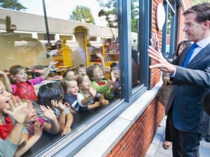 Dutch Prime Minister and Liberal Party leader Mark Rutte (R) waves at school children after casting his ballot for the Netherlands' general election at a voting station in The Hague September 12, 2012.
