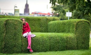 "A woman sits on a grass-made sofa in Frankfurt, Germany. The so-called ""Main-Sofa"" was initiated by Federal Minister for Environment Puttrich to highlight the upcoming event of ""Tag der Nachhaltigkeit"" (Day of Sustainability)."