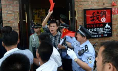 """Anti-Japanese demonstrators shout slogans as they leave a Japanese restaurant in Beijing after protesting over Tokyo's decision to buy the disputed islands in the East China Sea, known in Japan as the Senkaku Islands and in China as the Diaoyu Islands. China has dispatched two patrol ships to """"assert its sovereignty"""" over the islands at the centre of a row with Japan."""