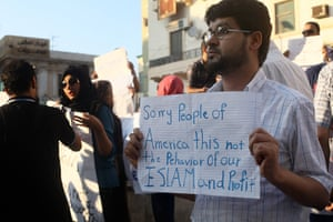Libya protests: A Libyan man holds a placard in English
