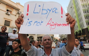Libya protests: A demonstrator holds placard during a rally