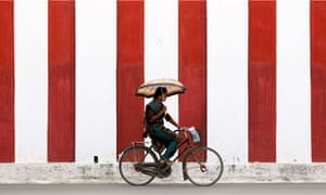A woman rides her bicycle on a road in Jaffna