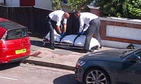 Police remove the body of a man believed to have fallen from the wheel well of a flight from Angola