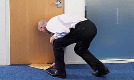 Businessman Passing Envelope Under Office Door
