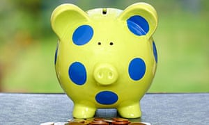 Green and blue spotted piggy bank with coins