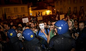Protesters face the riot police during a protest in front of the Portuguese Parliament following an online and broadly non-party political campaign against the new austerity measures, in Lisbon, on September 15, 2012.