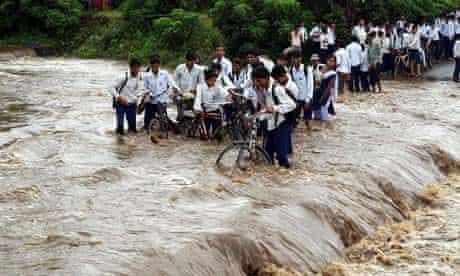 School children encounter flood water after heavy rains in Jhabua, central India