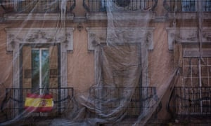 A Spanish flag hangs from the balcony of a building under repair in Madrid