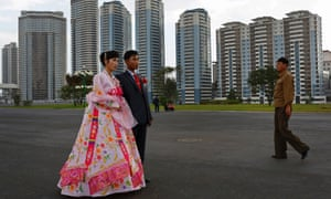 A North Korean couple pose for a wedding picture near the newly constructed development project area on Mansu Hill in Pyongyang.