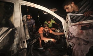 Palestinians inspect a destroyed car after an Israeli air strike in Rafah City southern Gaza Strip. Palestinian officials said an Israeli airstrike killed three Palestinian border patrol unit members.