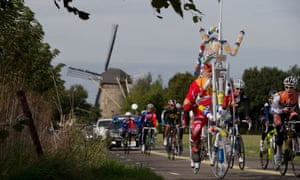 It must be thirsty work for cycling fan and bike constructor Didi Senft of Germany as he passes a windmill on the course of the road race of the Road World Championship Cycling near Valkenburg, southern Netherlands.