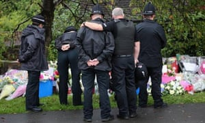 Police comfort each other near the scene of the shooting of two officers in Manchester