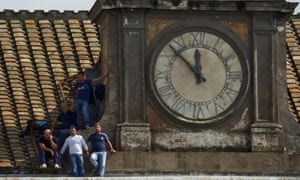 Five unemployed men protest about the economy as they stand on a ledge beneath the clock of the Royal Palace's bell tower in Naples. One of the protestors reached on the phone by journalists said 'we are five desperate fathers, because we can not even bring the bread at home'.