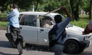 The anti-American protests are continuing around the world. Protesters use sticks to smash the windows of a car while marching towards the US embassy.