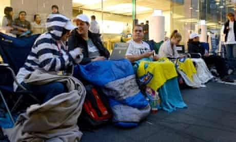 People sit in a queue outside Apple's flagship store in Sydney, Australia