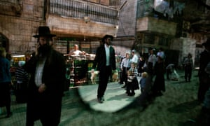 An ultra-Orthodox Jewish man carries live chickens he purchased in a market in the Mea Shearim neighborhood in Jerusalem in the run-up to Yom Kippur, the Day of Atonement.
