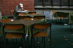 Kosovo art installation: An old man reads a newspaper outside a cafe