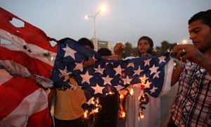 Followers of the Ansar al-Sharia brigade burn a US flag outside the Tibesti hotel in Benghazi, Libya