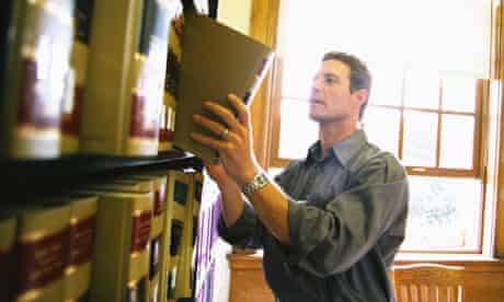 Man removing law book from library shelf