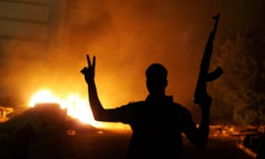 An armed Libyan man makes the victory sign in front of Ansar al-Sharia HQ in Benghazi