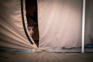 Syria Children: Nawara, five, peers out from her tent in Za'atari Refugee Camp, Jordan