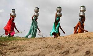 Women walk carrying metal pitchers