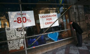 A man looks through the window of a store announcing a closing down sale in central Madrid September 24, 2012.