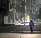 A Syrian man holds his robe while walking in the Salah al-Din neighbourhood