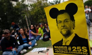 Demonstrators sit next to a sign with an image of Spanish Prime Minister Mariano Rajoy as they wait for the start of an assembly before an anti-austerity demonstration in Madrid September 25, 2012.