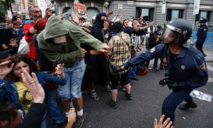 A policeman clubs a protester after police charged demonstrators outside the the Spanish parliament in Madrid, September 25, 2012.
