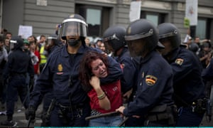 Riot policemen hold back a demonstrator during clashes around the Spanish parliament in a protest against spending cuts and the government of Mariano Rajoy on September 25, 2012 in Madrid, Spain.