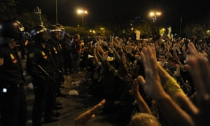 Riot policemen stand in front of a line of protesters.  Photograph: DOMINIQUE FAGET/AFP/Getty Images