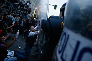 Madrid update: A demonstrator kneels before the riot police outside the Spanish parliament