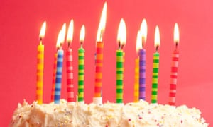 birthday cake with lots of cute striped candles shot on a red background