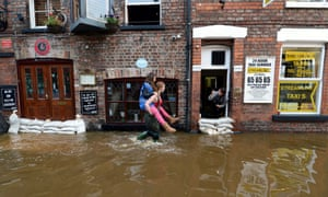 A woman gets a piggy back ride to avoid wet feet in the centre of York, as the River Ouse continues to rise today following the torrential rainfalls of the past few days.