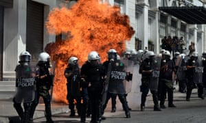 A fire bomb explodes behind a riot police squad on September 26, 2012 in Athens during clashes with demonstrators at a 24-hours general strike.