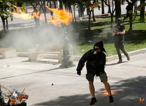 Greece protests update: A demonstrator throws a molotov cocktail to riot police officers