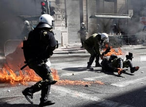 Greece protests update: A riot police officer is helped by a colleague after falling during clashes