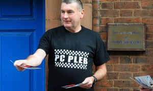 PC Mick Callaghan hands out leaflets outside the constituency offices of MP Andrew Mitchell, for the launch of a poster campaign against police cuts, in Sutton Coldfield, West Midlands.