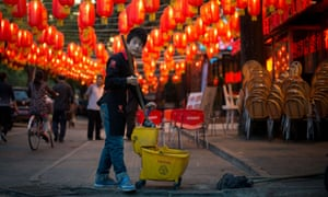 A restaurant worker cleans beneath lanterns hanging above a street ahead of the Mid Autumn Festival in Beijing.