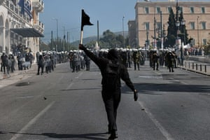Greece protests updates: A lone demonstrator waves a black flag in front of riot police