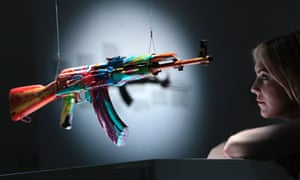 """A member of staff poses with an interpretation of an AK-47 assault rifle """"Spin AK47 for Peace One Day"""" by British artist Damien Hirst on display in an exhibition 'AKA Peace' at the Institute of Contemporary Arts in London."""