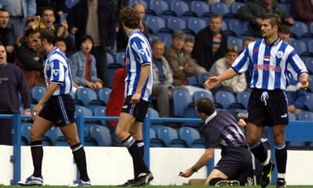 SHEFFIELD WEDNESDAY'S DI CANIO LEAVES THE PITCH WHILE REFEREE ALCOCK KNEELS ON THE GROUND.
