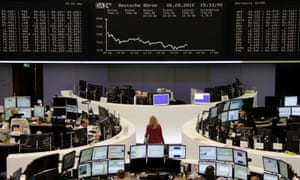 Traders are pictured at their desks in front of the DAX board at the Frankfurt stock exchange September 26, 2012.