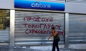 A woman covers her face to protect from teargas as she walks by a damaged Citibank branch following violent clashes between protesters and police in Athens' Syntagma square during a 24-hour labour strike September 26, 2012.