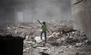 A Free Syrian Army fighter holds a rocket-propelled grenade launcher while taking cover after a tank blast in Aleppo, Syria. Syria's unrest began in March 2011 when protests calling for political change met a violent government crackdown.
