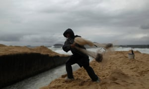 A fisherman throws his net at the Ipanema beach in Rio de Janeiro. According to local media, temperatures have fallen down to about 16 degrees and winds could reach speeds of almost 76 km (47 miles) per hour.
